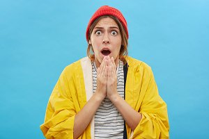 Headshot of amazed emotional young female in yellow raincoat and red hat posing against blank blue wall background with jaw dropped and eyes popped out, taken by surprise. Human reaction and attitude