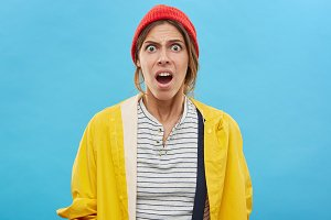 Waist up portrait of shocked or frustrated fashionable young woman standing at blue studio wall, having puzzled and surprised expression on her face. Funny girl opening mouth in shock and astonishment