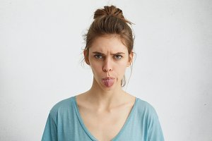 Angry young female showing her digust and distaste having gloomy expression demonstaring tongue refusing to do something. Furious beautiful woman with upset look rejecting her guilt isolated on white