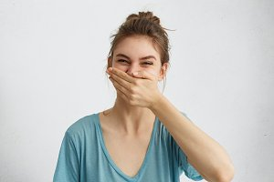 Positive female laughing while having good mood during spare time trying to control her emotions covering mouth with hand. Cheerful woman having fun bursting into laughing keeping hand on mouth