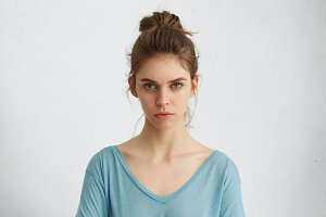 Portrait of naturally beautiful female having dark hair tied in knot wearing blue casual blouse looking seriously into camera while posing against white background. Facial expression and body language