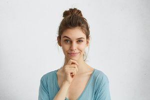 Headshot of beautiful female having cunning look raising her eyebrow and holding hand on chin having some tricky plans in her mind. Young lady looking playfully and sly isolated over white wall