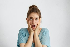 Horrified woman with attractive appearance looking scared keeping her mouth opened realizing that she has big problems. Stressful female posing in studio expressing negative emotions and feelings