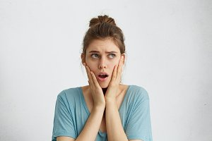 Stunned woman with hair knot wearing casual blue blouse holding hands on cheeks opening her mouth with surprise looking up while posing agaist white studio wall. People, facial expressions, emotions