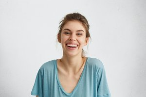 Portrait of glad woman with blue eyes smiling in camera sincerely rejoicing her future wedding with boyfriend. European woman with broad smile in blue casual blouse posing against white background