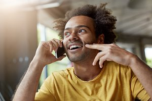 Picture of good-looking happy African man with beard and curly hair smiling cheerfully while talking on mobile phone, having interested look, listening to his interlocutor attentively. Film effect