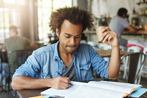 Indoor shot of serious handsome black male student drinking coffee while working on home assignment, writing down in copybook using pen, looking at notes with focused expression and pursuing lips