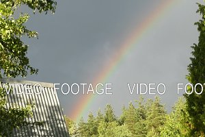 Rainbow in the sky, the roof of the house and the tree