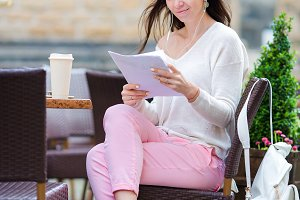 Beautiful woman sitting in a cafe outdoor drinking coffee. Happy tourist with newspaper at openair restaraunt