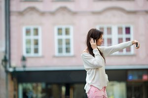 Young caucasian woman taking self portrait in european city