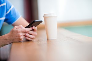 Closeup cellphone and glass of coffee in cafe. Man using mobile smartphone. Boy touching a screen of his smarthone.