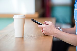 Closeup of male hands holding cellphone and glass of coffee in cafe. Man using mobile smartphone. Boy touching a screen of his smarthone.