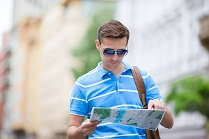 Man tourist with a city map and backpack in Europe street. Caucasian boy looking with map of European city.
