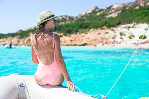 Beautiful young woman relaxing on the boat in amazing turquoise lagoon