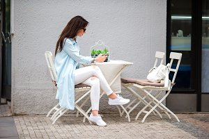 Beautiful woman sitting in a cafe outdoor drinking coffee. Happy tourist with cellphone at openair restaraunt