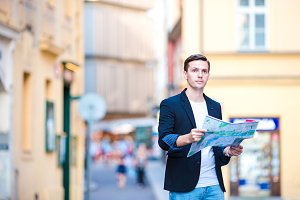 Man tourist with a city map in Europe. Young guy looking at the map of European city in search of attractions.