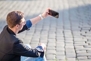 Close up of male hands is holding cellphone outdoors on the street. Man using mobile smartphone.