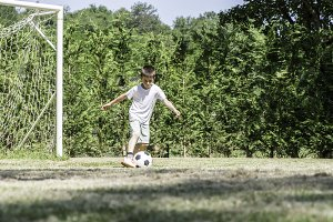 Child playing football in a stadium