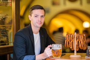 Young man with pint of beer and salted soft pretzels in beer sport bar