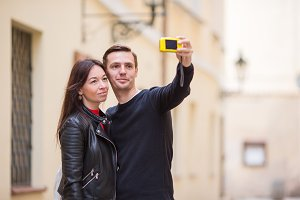 Young couple traveling on holidays in Europe smiling happy. Caucasian family making selfie in european empty old streets