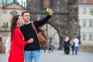 Young couple traveling on holidays in Europe smiling happy. Caucasian family making selfie in popular Karlov Most
