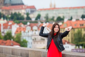 Happy young urban woman in european city on the famous bridge. Caucasian tourist walking in Prague, Czech Republic
