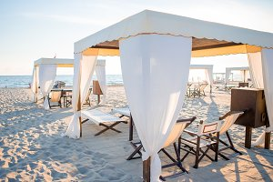 Wooden sunbeds in front of a turquoise sea in the evening light. Sunbeds in famous italian sand beach at Forte dei Marmi
