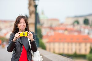 Happy young woman in european city on the famous bridge. Caucasian tourist take a photo by her camera in Prague
