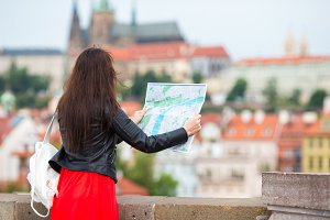 Happy young woman with a city map in Europe. Travel tourist woman with map outdoors during holidays in Europe.