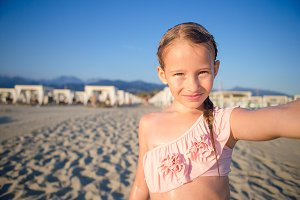 Happy little girl taking selfie at tropical beach on exotic island during summer vacation