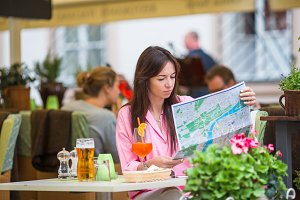 Beautiful woman sitting in a cafe outdoor with map. Happy tourist enjoy european holidays at openair restaraunt