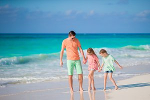 Family of dad and kids on white tropical beach have a lot of fun