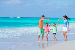 Beautiful family have a lot of fun on the beach