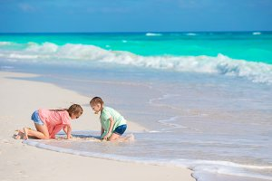 Adorable little kids play with white sand