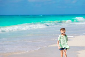 Happy little girl walking on the white beach