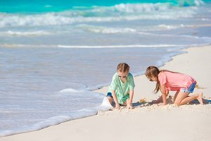 Adorable little kids having fun together drawing on the sand on white beach