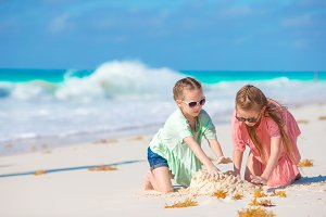 Adorable little girls have fun together on white beach