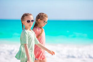Adorable little girls having fun together on white beach