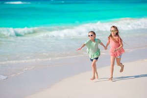 Kids enjoy their holidays on the beach running and having fun