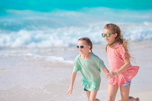 Adorable little girls have fun together on white tropical beach