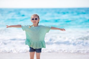 Happy little girl walking at beach during caribbean vacation