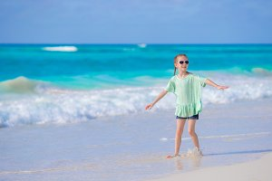Cute little girl walking at beach during caribbean vacation