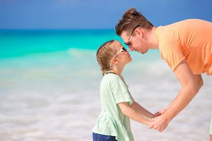 Portrait of little adorable girl and young father at tropical beach