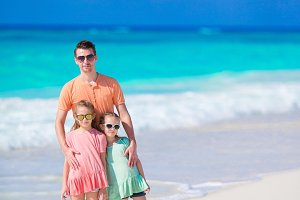 Family of father and kids on white tropical beach