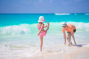 Little girl and happy dad having fun in the water on the beach