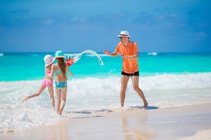 Happy family at tropical beach having fun