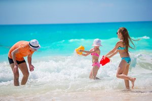 Little girls and happy dad having fun during beach vacation