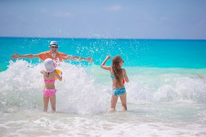 Little girls and happy dad having fun on the seashore swimming and running