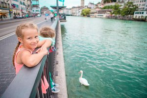 Adorable little girls outdoors in Zurich, Switzerland. Kids in beautiful city near river and swans