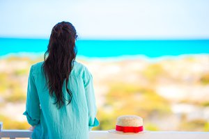 Young woman on balcony with view on a tropical beach